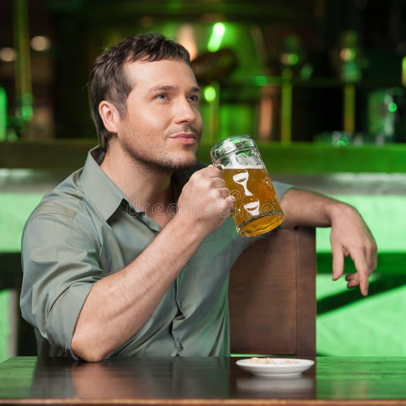 Probar una buena cerveza. Retrato de los hombres pensativos que beben la cerveza en imagen de archivo