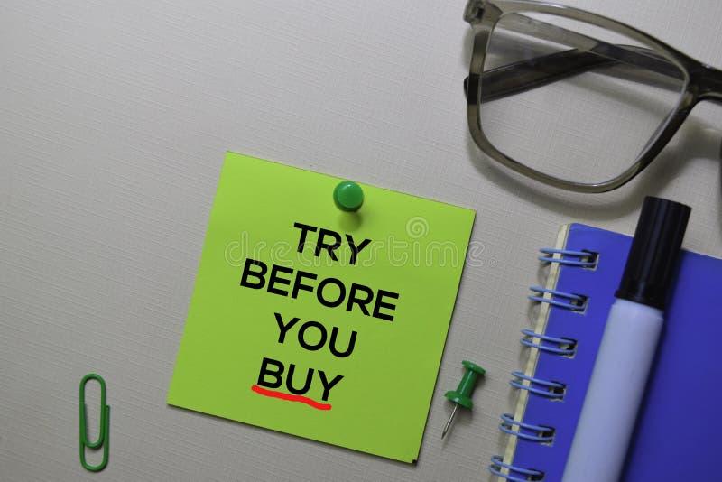 Probeer alvorens u tekst op kleverige die nota's koopt op bureau worden geïsoleerd stock foto