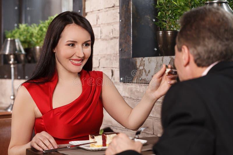 Probeer deze cake! Mooie rijpe vrouwen die in rode kleding haar B voeden stock afbeelding