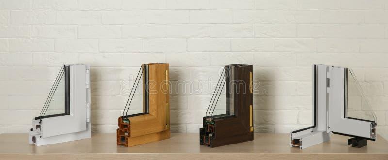 Proben von modernen Fensterprofilen auf Tabelle gegen Backsteinmauer lizenzfreies stockfoto