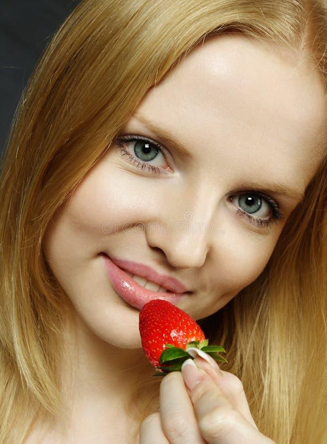 Probierenerdbeere der jungen Frau stockfotos