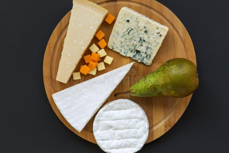 Probierenkäse mit Birne auf hölzernem Brett auf dunklem Hintergrund Lebensmittel für romantisches Flache Lage lizenzfreie stockfotos