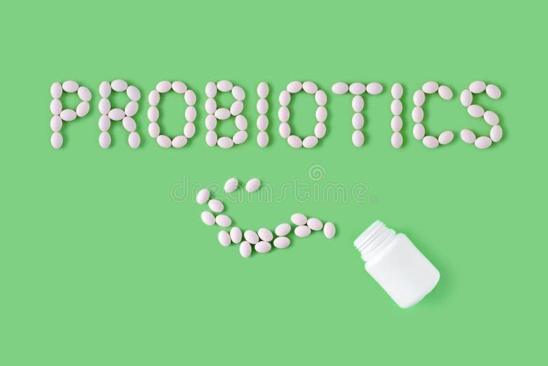 Probiotics词由药片做成在绿色背景 平的位置,顶视图,赠送阅本空间 库存照片