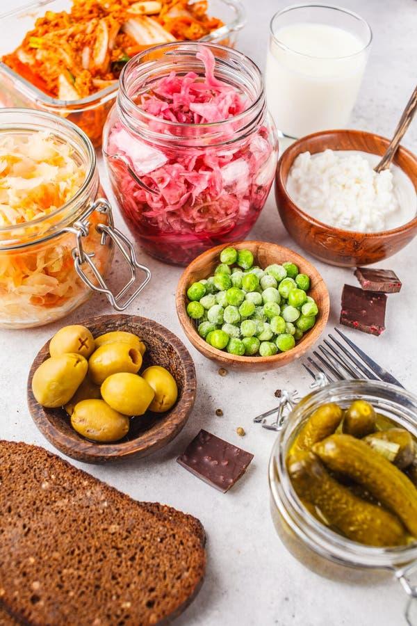 Probiotics food concept. Kimchi, beet sauerkraut, sauerkraut, cottage cheese, peas, olives, bread, chocolate, kefir and pickled stock photography