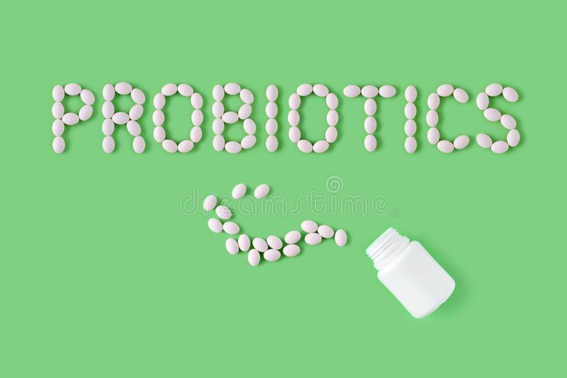 Probiotics word made of pills on green background. Flat lay, top view, free copy space. stock photos