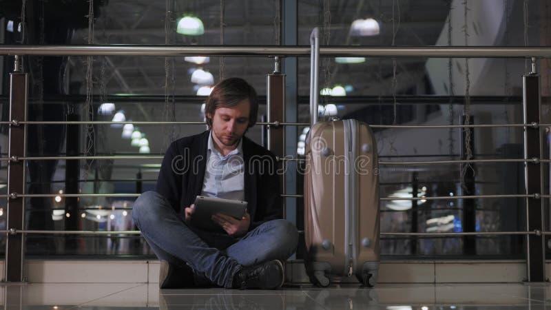Probleem met vervoer, vertraging van vlucht, de gedeprimeerde mens zijn bagage en tablet, hoofdpijn rode ogen stock foto