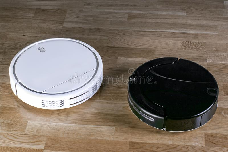 Two different robotic vacuum cleaners models cleaning dust on laminate floors. Modern smart cleaning technology housekeeping. royalty free stock photos