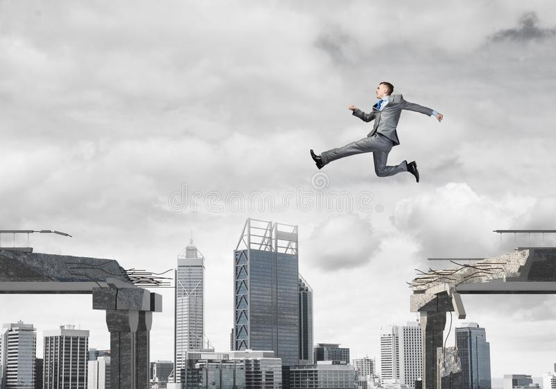 Problem and difficulties overcoming concept. Businessman jumping over gap in concrete bridge as symbol of overcoming challenges. Dark sky and cityscape on stock photo