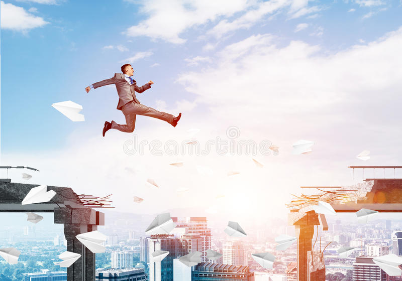 Problem and difficulties overcoming concept. Businessman jumping over gap with flying paper planes in concrete bridge as symbol of overcoming challenges stock photos