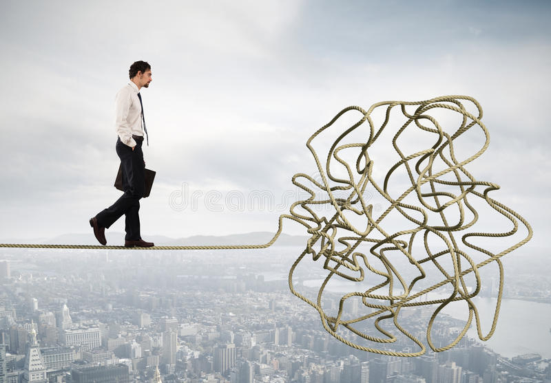 Problem and difficulty concept with tangled rope. Problem and difficulty concept with a businessman who walk on a tangled rope royalty free stock photography