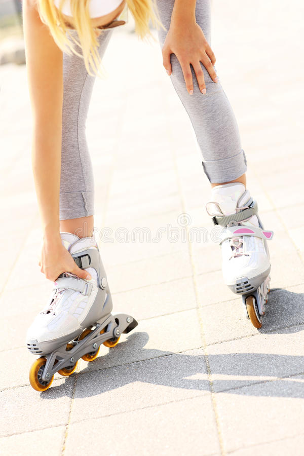 Problem with foot while roller blading. A picture of a woman having problem with ankle while roller blading royalty free stock photos