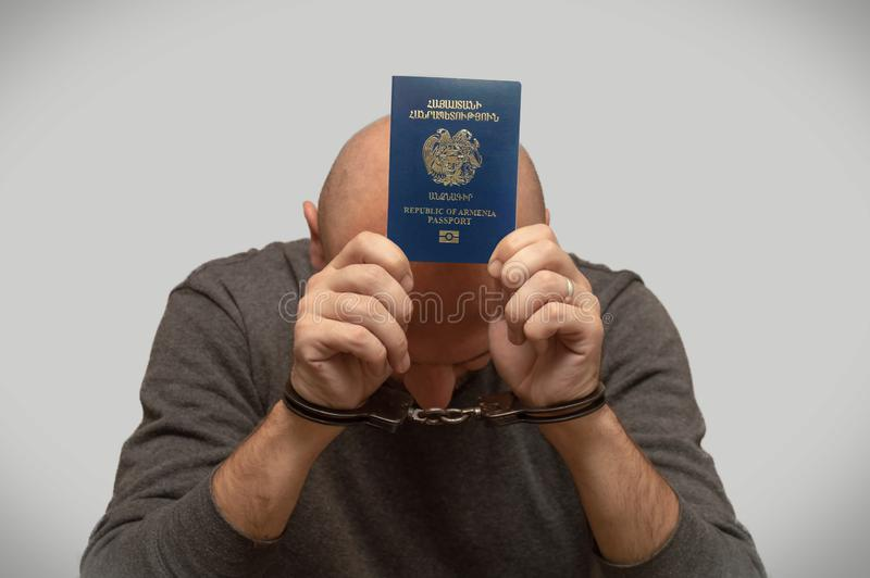 The problem of illegal immigration of refugees from Armenia, an Armenian immigrant in handcuffs. Illegal border crossing, border t. Respasser arrested royalty free stock photography