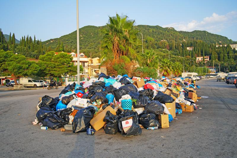 Problem med avskrädeackumulation i nedgrävningarna av sopor för gator som tack vare stängs i Benitses, ett fiskeläge i Korfu fotografering för bildbyråer