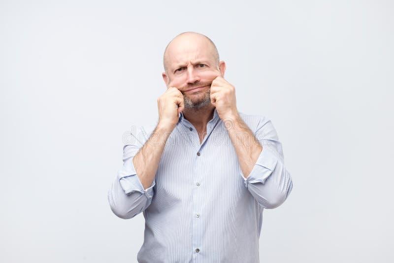 Problem med hud och skrynklor Stilig caucasian man i den vita skjortan som sträcker hans hud på framsida royaltyfri fotografi