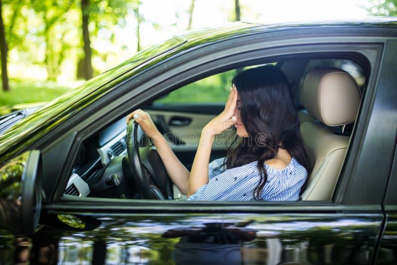 Problem på vägen, flicka trycker på hennes panna vid händer medan i hennes bil arkivfoto