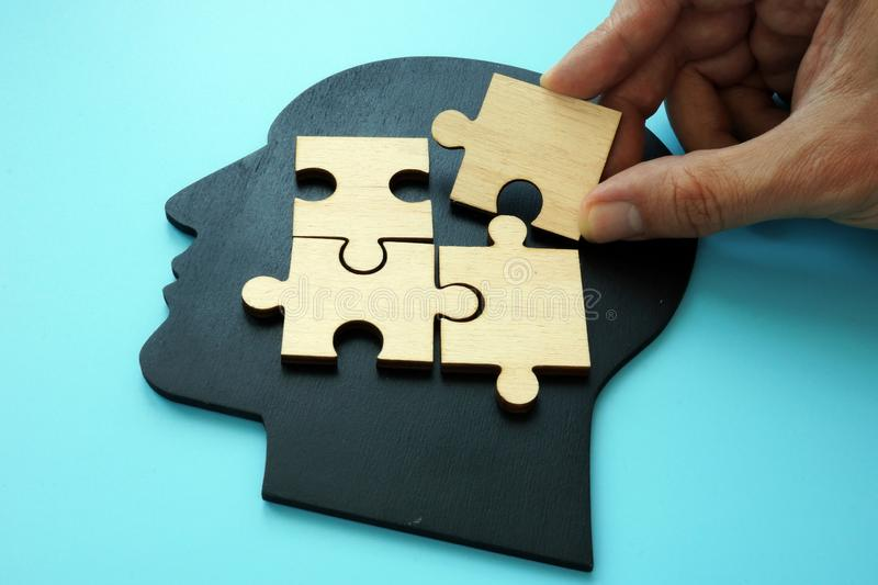 Problem solving concept. Hand puts piece of puzzle on head shape royalty free stock photo