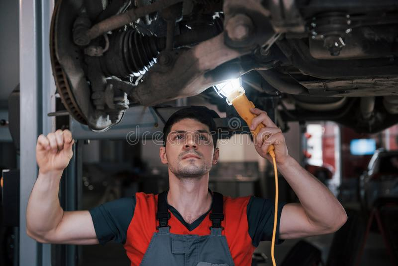 Problem will be solved very soon. Man at the workshop in uniform fixes broken parts of the modern car royalty free stock photos