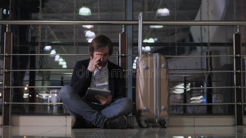 Problem z transportem, opóźnieniem lot, deprymującym mężczyzna i pastylką, jego bagaż, migreny czerwień ono przygląda się obrazy royalty free