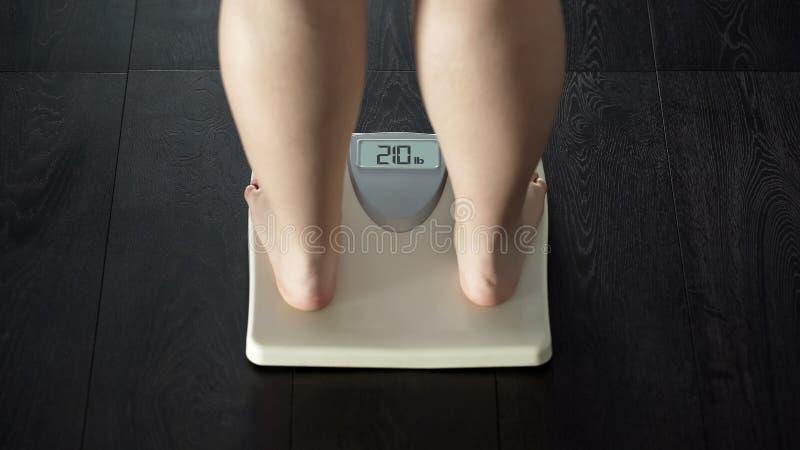 Problema adicional del peso, situación femenina gorda en escalas, obesidad, vista posterior imagen de archivo