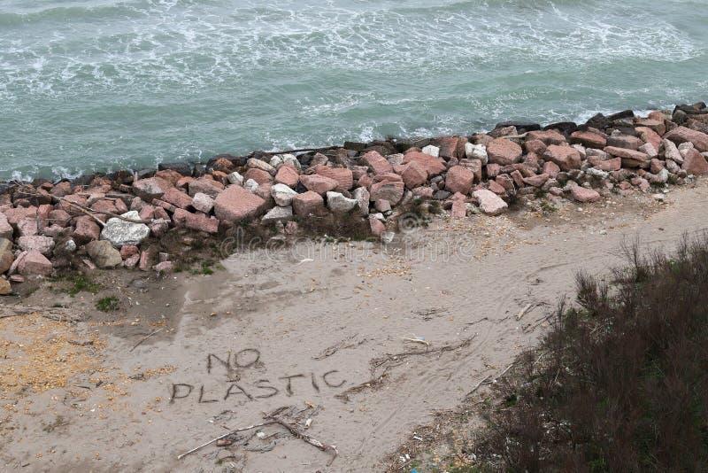 Problema ambiental Concepto de la ecolog?a Pl?stico en la playa con la escritura el SOS Basura derramada en la playa foto de archivo libre de regalías