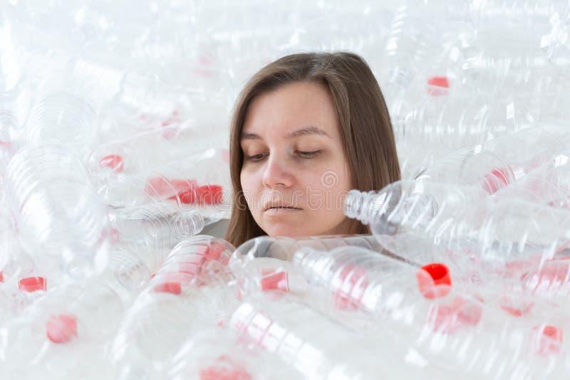 Problema de la contaminaci?n y protecci?n del medio ambiente pl?sticos Mujer cansada d?bil en una pila de botellas pl?sticas Ahor foto de archivo