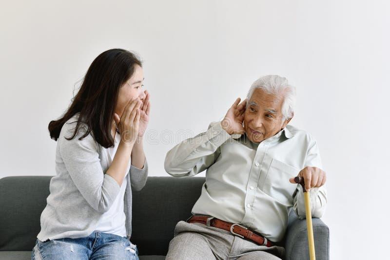 Problema de la pérdida de oído, viejo hombre asiático con la mano en el gesto del oído que intenta escuchar mujer de grito fotos de archivo