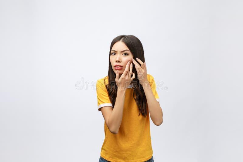 Problema de piel de la cara - tacto infeliz de la mujer joven su piel, concepto para el cuidado de piel, asiático fotos de archivo libres de regalías