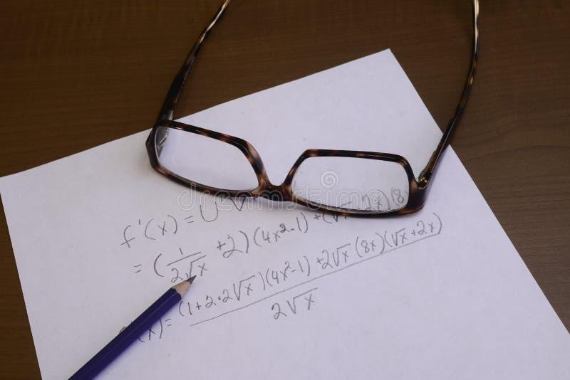 Problema del cálculo que es resuelto para encontrar una solución con el papel y el lápiz foto de archivo libre de regalías