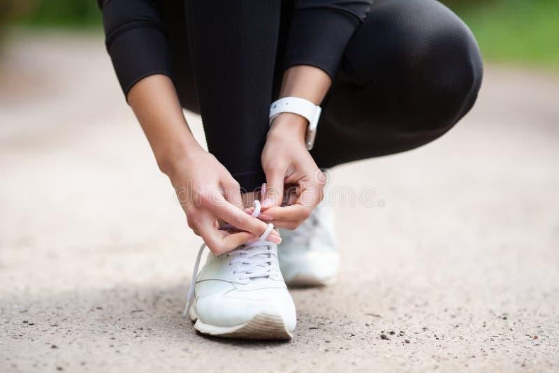 Problema delle scarpe da tennis Corridore femminile che lega le sue scarpe che preparano per un trotto fotografie stock