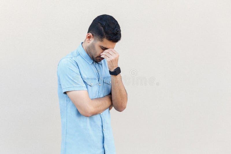 Problema, depressione o malattia Ritratto da solo di giovane uomo barbuto bello triste nella condizione blu della camicia, tenent fotografie stock