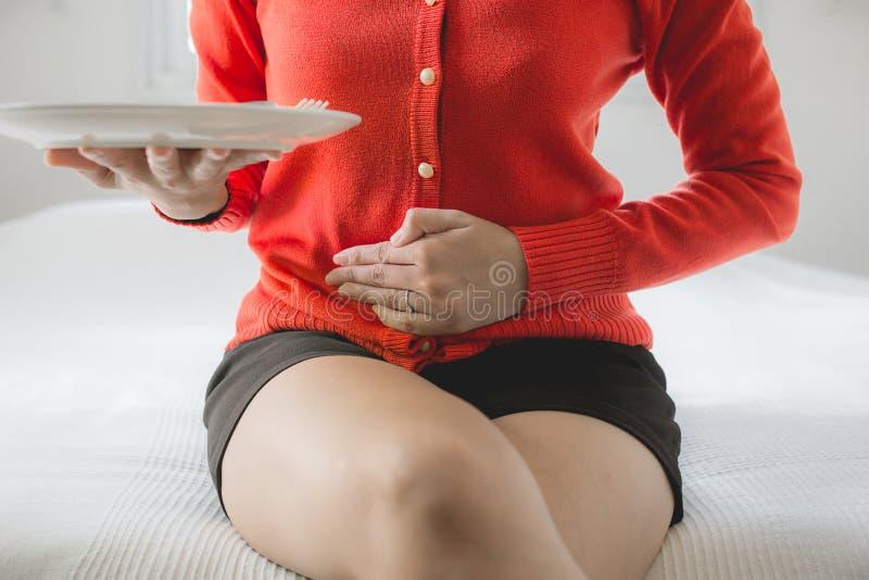 Problemas da digestão, mulher com dor de estômago após comer, fêmea da mão que guarda sua barriga fotografia de stock royalty free