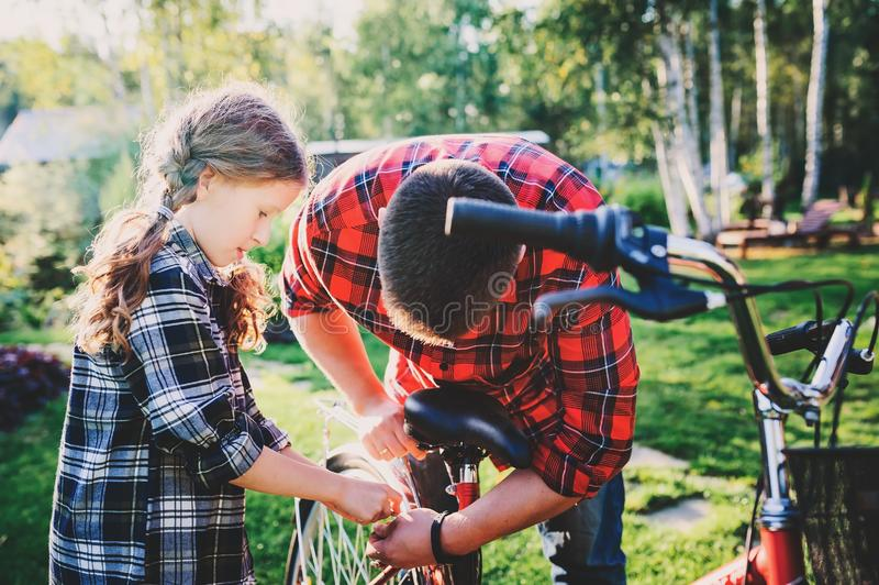 Problemas da fixação do pai e da filha com a bicicleta exterior no verão foto de stock