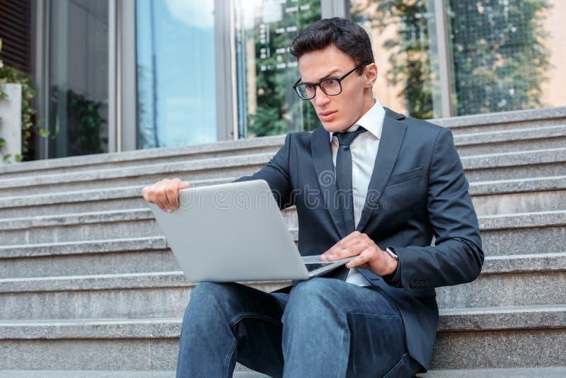 Problemas da tecnologia Homem de negócios nos monóculos que sentam-se em escadas na rua da cidade que olha tela do portátil confu fotografia de stock