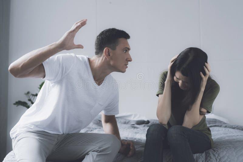 Problemas de la familia Un hombre balancea para golpear a una mujer que se siente al lado de él en la cama y se cubra con sus man fotos de archivo