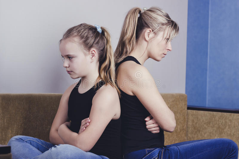 Problemas do adolescente - adolescente irritado e sua mãe preocupada que sentam-se de volta à parte traseira imagens de stock