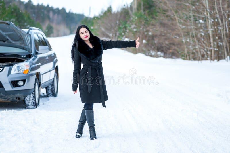 Problemas hermosos jovenes de la señalización de la mujer con el coche quebrado en triunfo imágenes de archivo libres de regalías