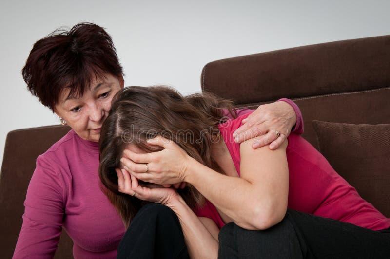 Problemas - la madre mayor conforta a la hija imagenes de archivo