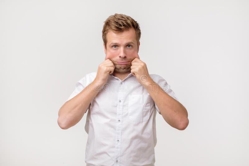 Problemen met huid en rimpels Knappe Kaukasische mens in wit overhemd die zijn huid op gezicht uitrekken stock foto
