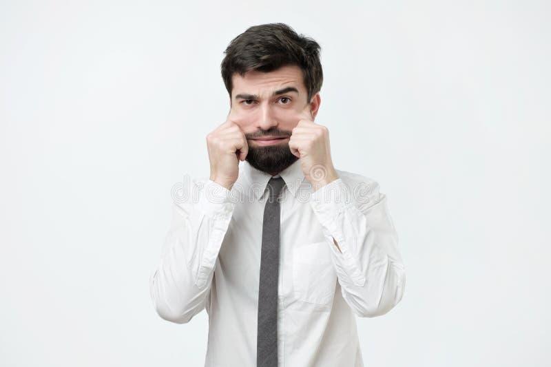 Problemen met huid en rimpels Knappe Spaanse mens in wit overhemd die zijn huid op gezicht uitrekken stock afbeelding