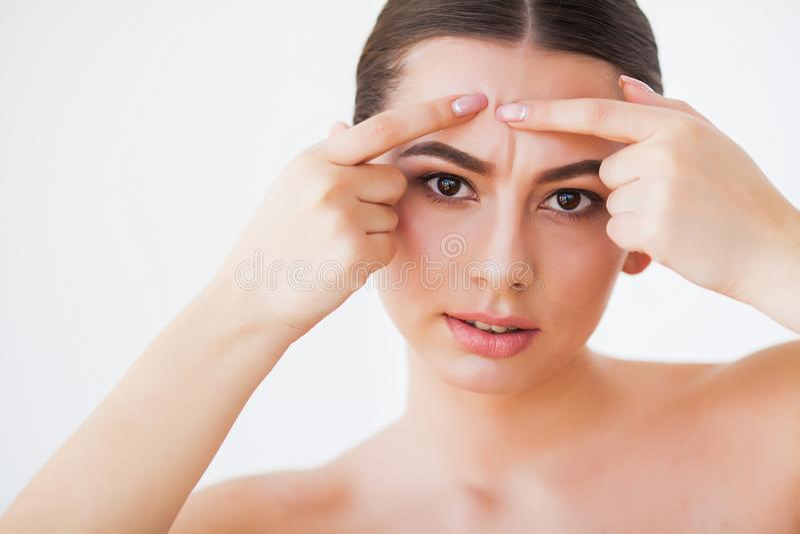 Problemhaut Frau, die Stelle auf Gesicht zerquetscht und im Spiegel schaut stockbilder