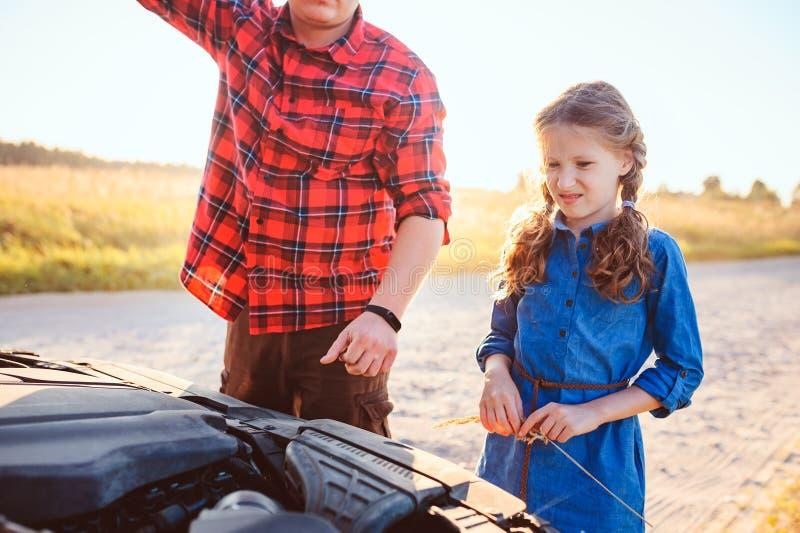 Problemi della riparazione della figlia e del padre con l'automobile durante il viaggio stradale di estate fotografia stock libera da diritti