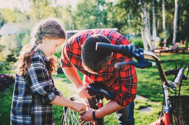 Problemi della riparazione della figlia e del padre con la bicicletta all'aperto di estate fotografia stock
