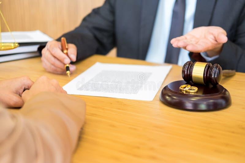 Problemi delle coppie che si siedono un martelletto dorato del giudice delle fedi nuziali di matrimonio che decide sui documenti  fotografia stock