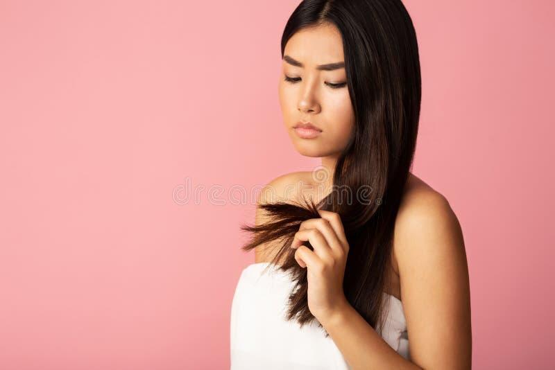 Problemi di cura di capelli La tenuta della ragazza ha danneggiato i capelli spaccati immagini stock