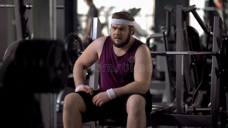 Problemi di pensiero del sovrappeso dell'uomo grasso turbato, desiderio di perdere peso, allenamento della palestra fotografie stock libere da diritti