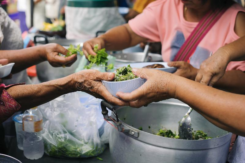 Problemi sociali di povertà aiutati alimentandosi: Il concetto di donare alimento al povero nella società fotografie stock libere da diritti
