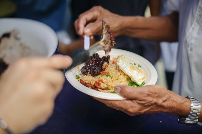 Problemi sociali di povertà aiutati alimentandosi: Il concetto di donare alimento al povero nella società immagini stock libere da diritti