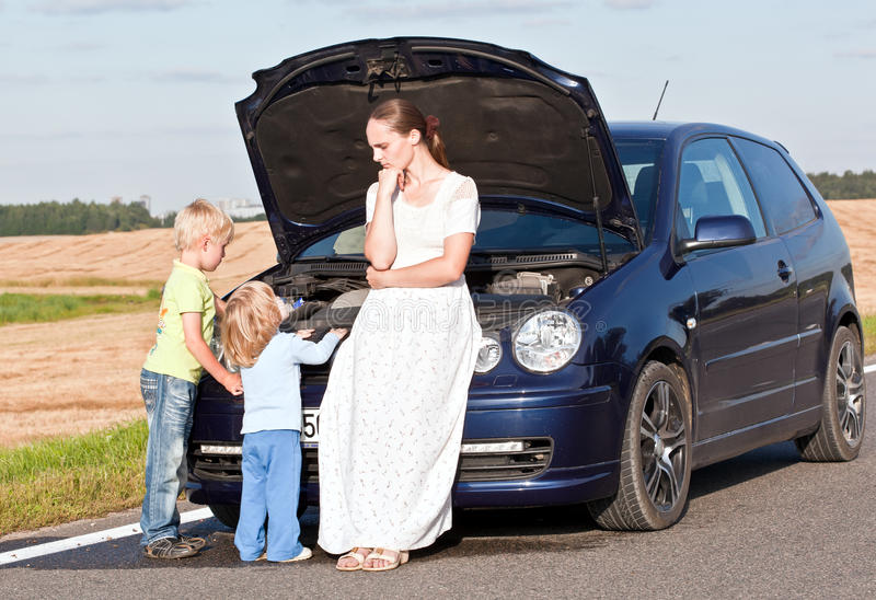 Problems with the car. Young white female with two children having car trouble royalty free stock photo