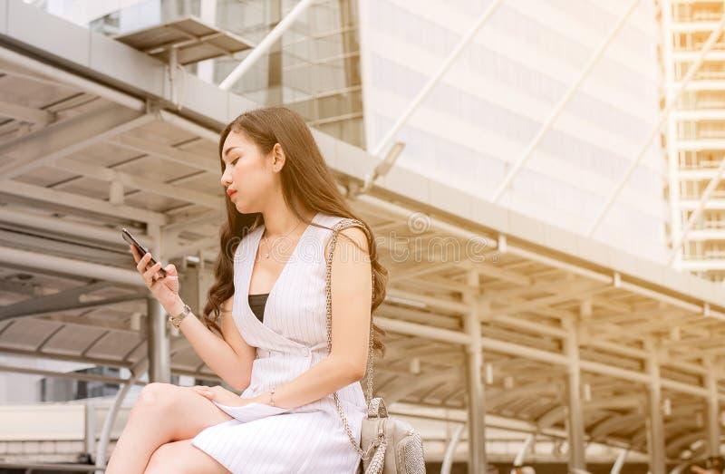 Problems- der Arbeitslosigkeitkonzept, asiatisches Schönheitsverbindungsinternet neuen Job am Handy beim Sitzen finden im Freien stockbild