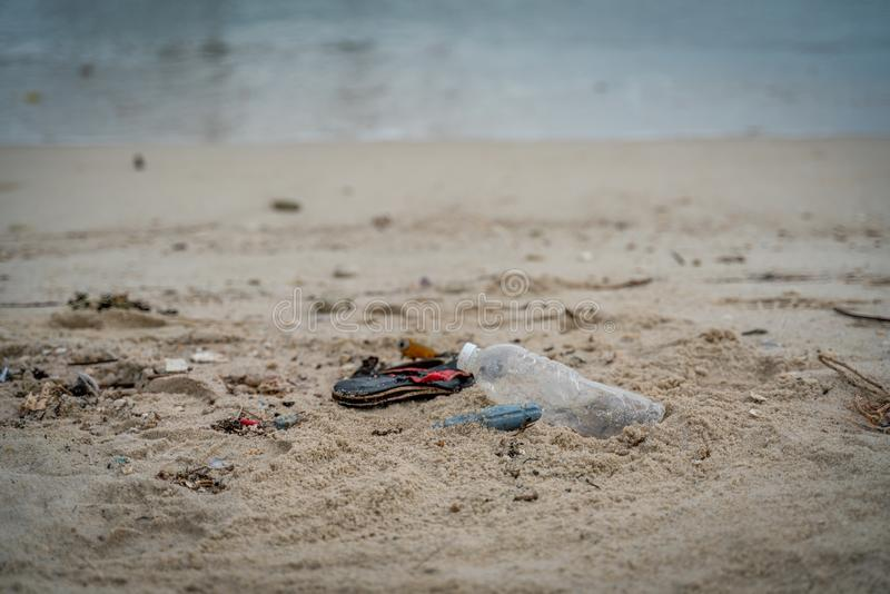 Problems of environmental pollution and oceans, plastic trash on the beach, bottles and slippers. Dirty sea shore stock photo